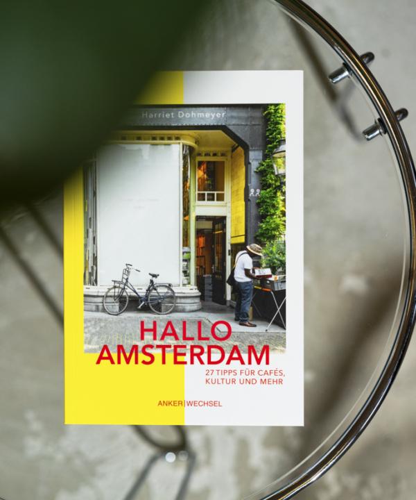 """""""Hallo Amsterdam"""" – Ankerwechsel Verlag Buch im Studio von Ain't No Trash auf Glastisch mit Pflanze"""