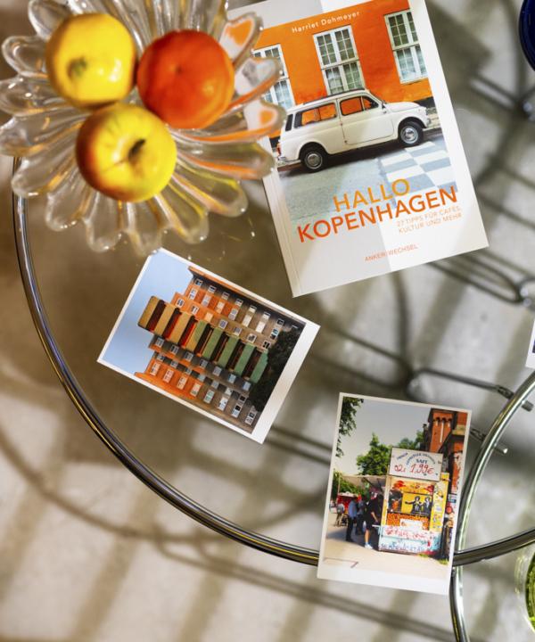 """""""Hallo Kopenhagen"""" – Ankerwechsel Verlag Buch im Studio von Ain't No Trash auf Glastisch mit Postkarten und Obstschale"""