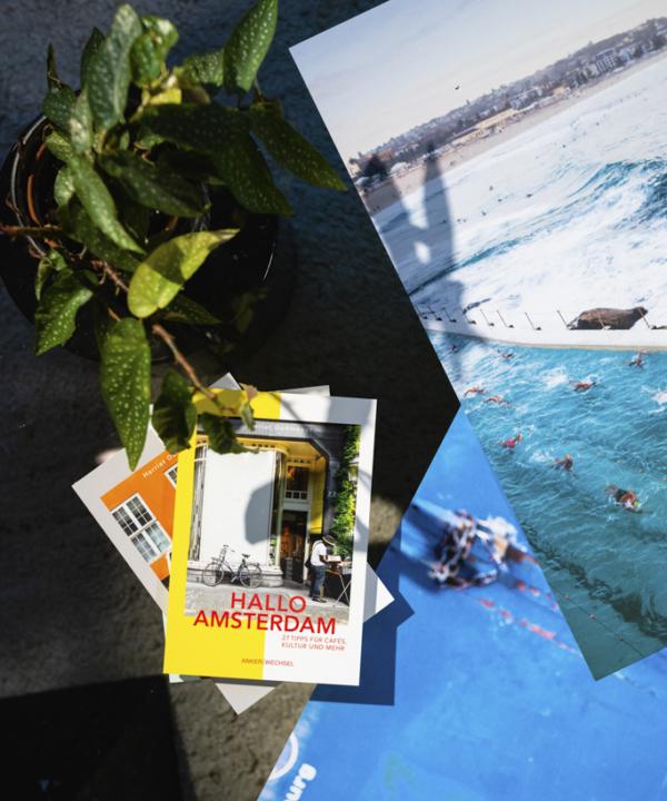 """""""Hallo Amsterdam"""" – Ankerwechsel Verlag Buch im Studio von Ain't No Trash auf Glastisch mit limitierten Fotodrucken und Pflanze"""