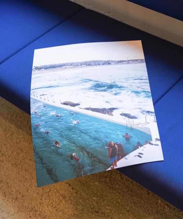 """""""Bondi Beach"""" Poster: Ankerwechsel-Verlag-Limitierter-Fotodruck-Ain't-No-Trash-Studio auf blauem Vintage-Sofa"""