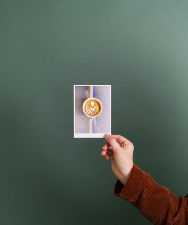 """Postkarte: """"Kaffee-Regenbogen-Tornqvist-Coffee-Hamburg""""in der Hand vor grünem Hintergrund"""