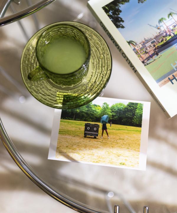 Postkarte: Vondelpark Container Amsterdam auf Glastisch mit grüner Tasse