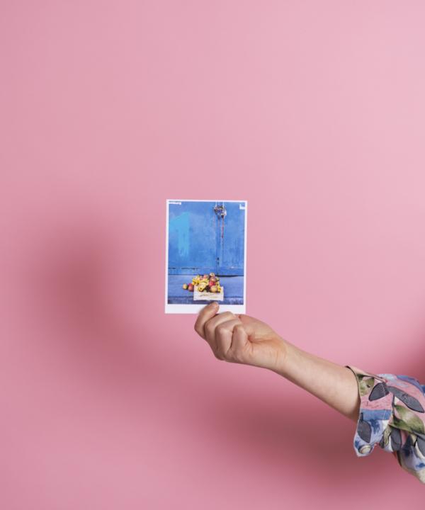 """Postkarte: """"Obstkiste-Äpfel-Bananen"""" Hamburg-Oberhafen-blau vor pinkem Hintergrund mit Hand"""