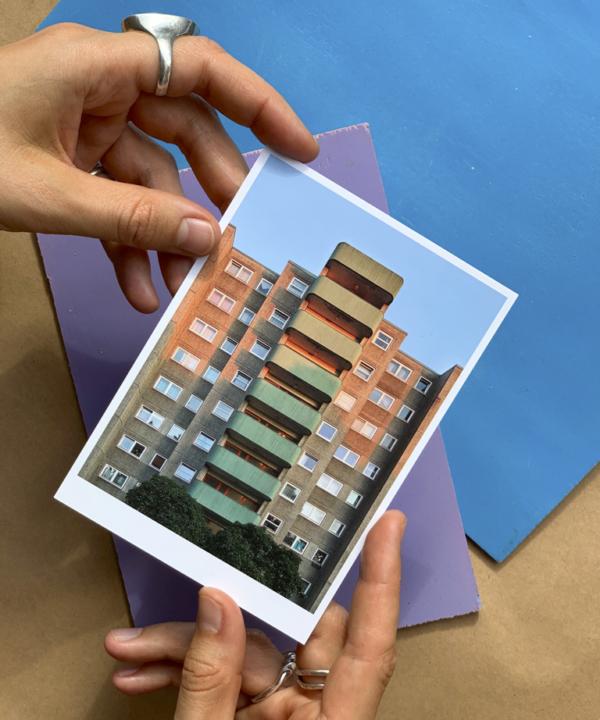 Berlin-Wedding-Kunstdruck-Postkarte: Beton Plattenbau in der Hand mit Briefumschlägen