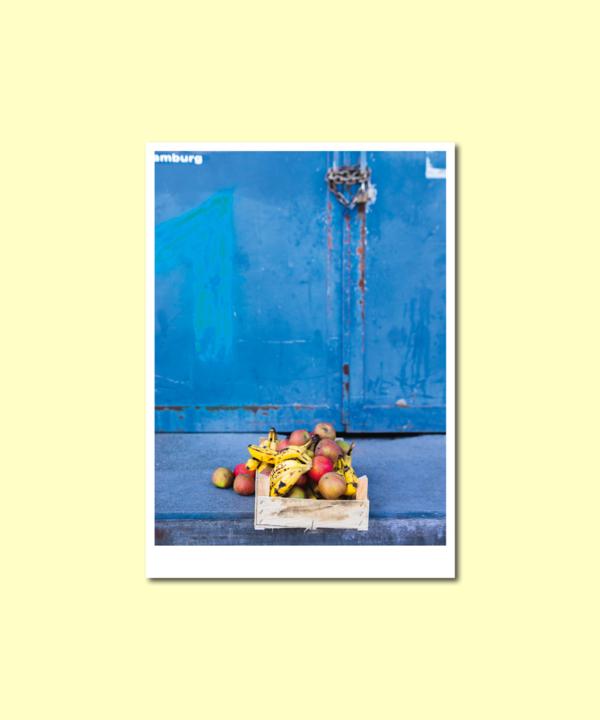 """Postkarte: """"Obstkiste-Äpfel-Bananen"""" Hamburg-Oberhafen-blau-Vorderseite auf gelbem Hintergrund"""