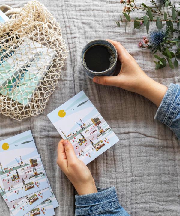 """Ankerwechsel """"Hamburg illustriert"""" Postkarte auf gelbem Hintergrund von Saskia Rasink in der Hand mit Kaffee"""